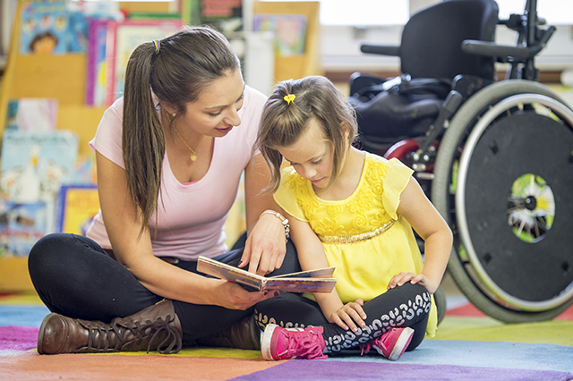 Carer reading to young girl with wheelchair in background.jpg