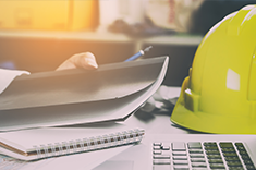 Image of construction hardhat and paperwork
