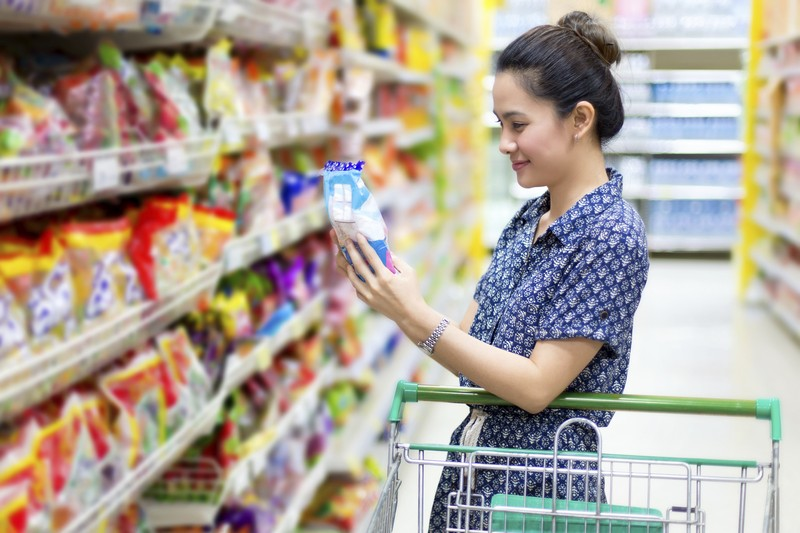 Woman looking at grocery item in supermarket.