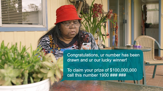 Lady looking at sms on her phone. Message reads: 'Congratulations, ur number has been drawn and your our lucky winner! To claim your prize of $100,000,000 call this number 1900 ### ###'