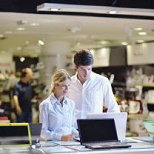 Man and woman looking at laptops in store