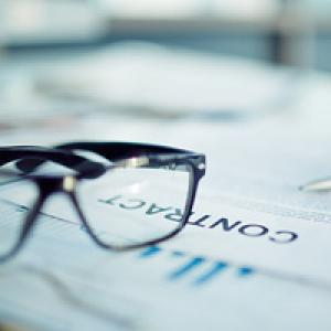 Glasses resting on contract paperwork