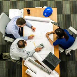 Three people sitting around work desk
