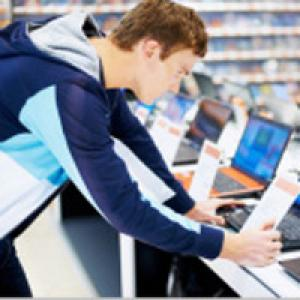 Man looking at laptop in store