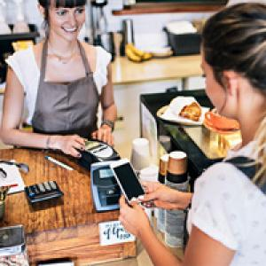 Woman purchasing items from staff at a cafe
