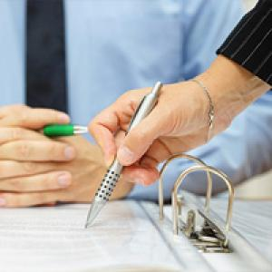 Person pointing to where businessman should sign