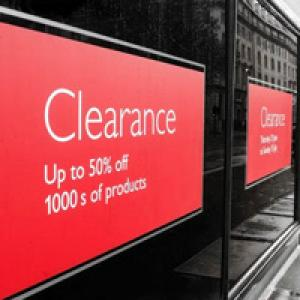 Clearance sign in shop window saying 50 per cent off