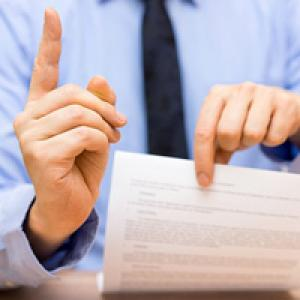 Business person holding paperwork and shaking finger