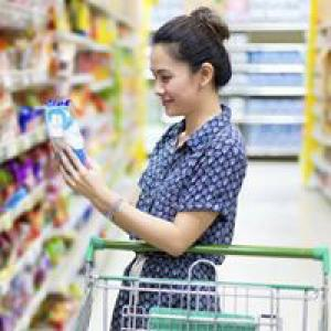 Woman with trolley looking at products in supermarket
