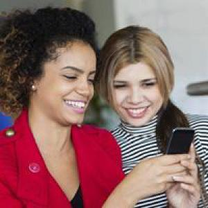 Two women looking at mobile phone screen