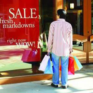 Man holding shopping bags looking at sale sign