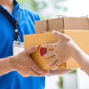 Delivery person handing box to consumer