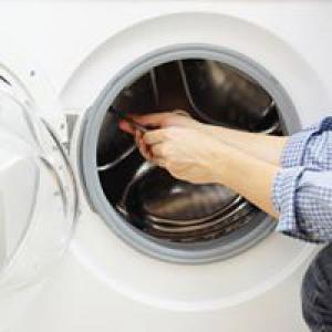 Hands fixing washine machine