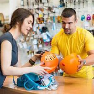 Woman and man comparing bike helmets in shop