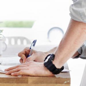 Hands signing paperwork on table