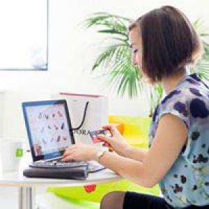 Woman sitting at computer with shoppings bags