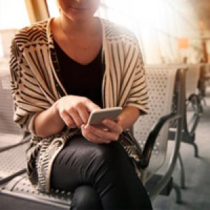 Woman sitting in airport using mobile phone