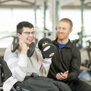 Man in wheelchair and personal trainer